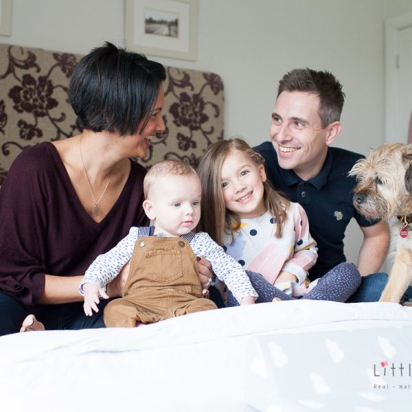 kids together having fun with dog on bed