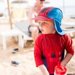 boy dressed as spiderman on the beach