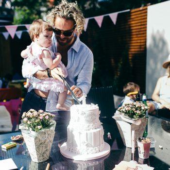 man cutting daughters birthday cake