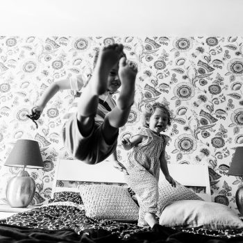 kids having fun jumping on bed