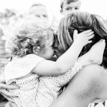 mum lovingly hugging daughter and kissing