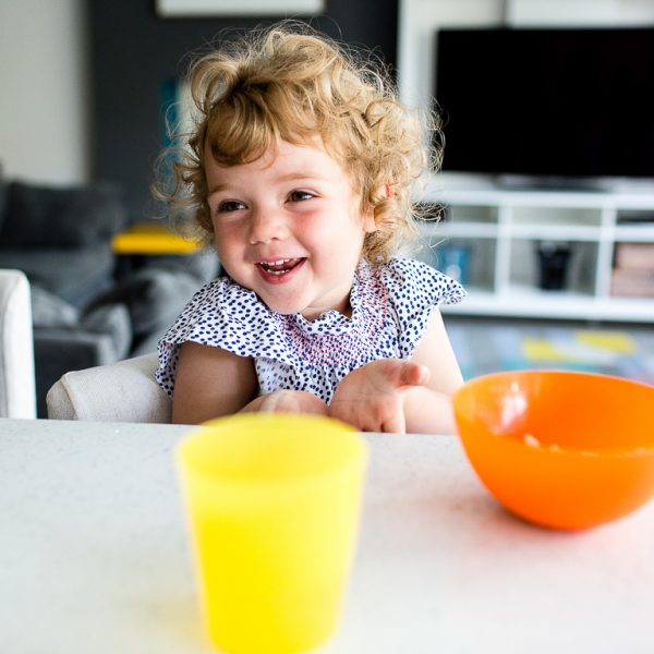 girl eating snack in kitchen with family