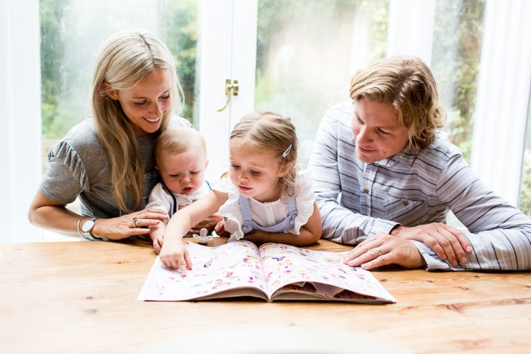 family reading book together in kitchen