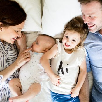 family relaxing on bed during photo shoot