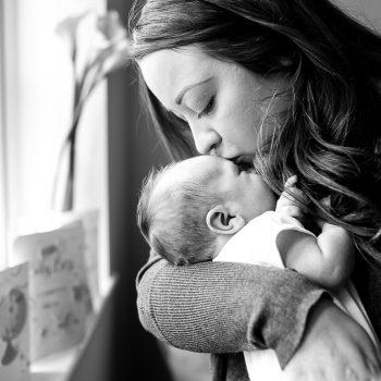 mum kissing newborn baby boy head by window