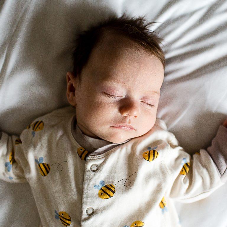 weeks old baby sleeping peacefully on bed