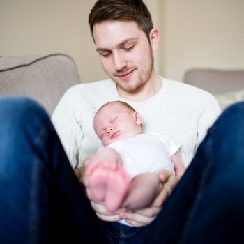 newborn baby in dads arms fast asleep