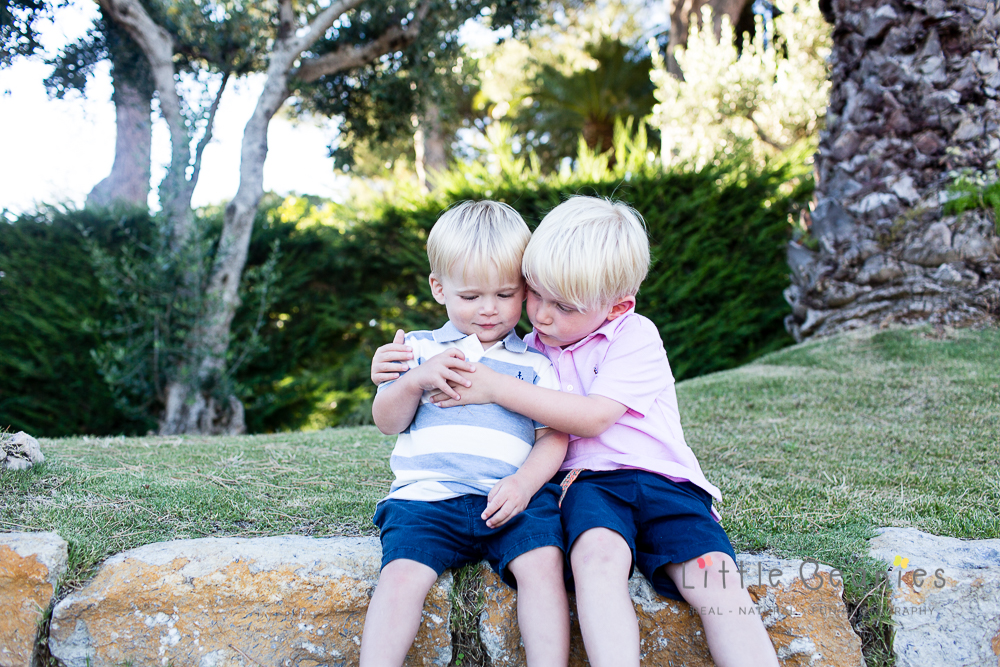 boys cuddling on steps on holiday having family photo