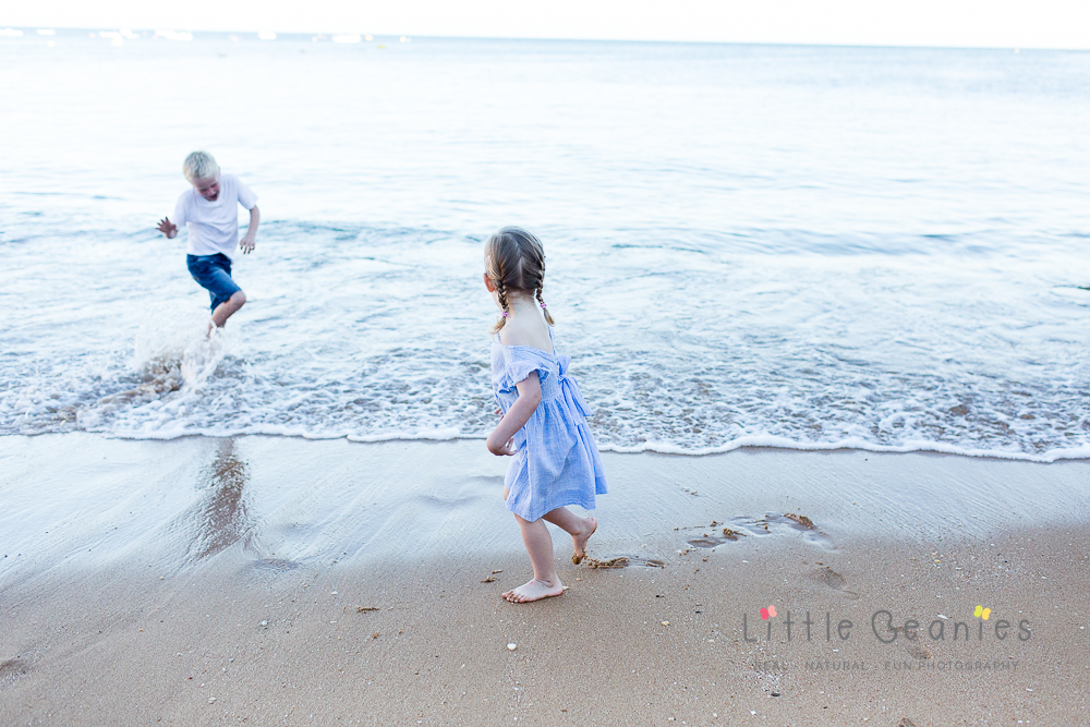 brother and sister playing on the beach and splashing in the waves whilst having their professional family photo taken