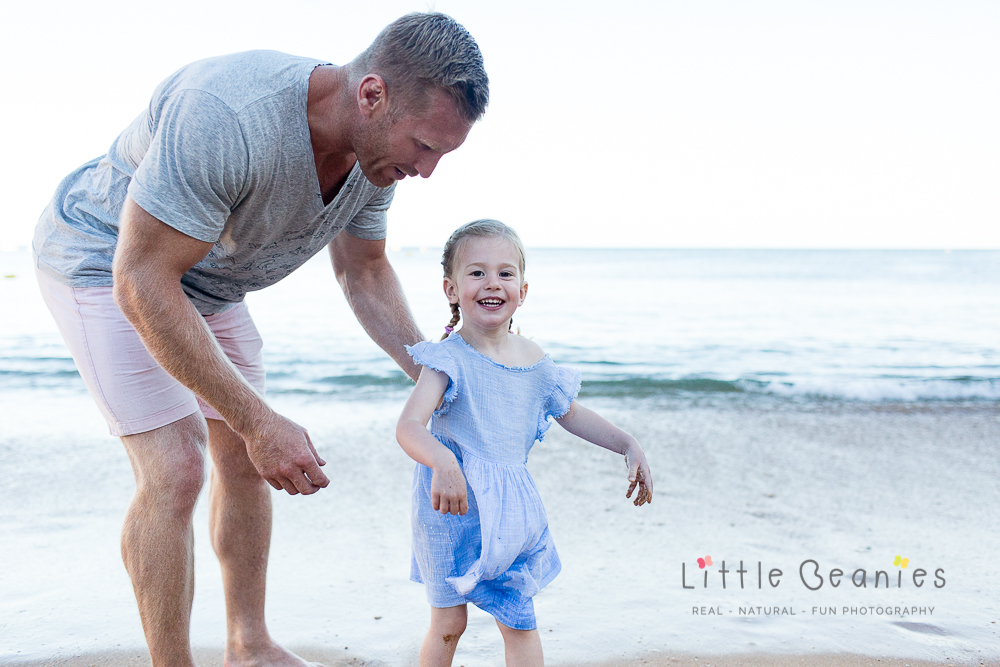 girl laughing on the beach with daddy