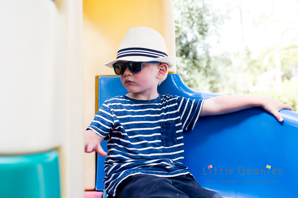 boy looking grown up on slide on holiday with Lisa Jordan from Little Beanies Photography