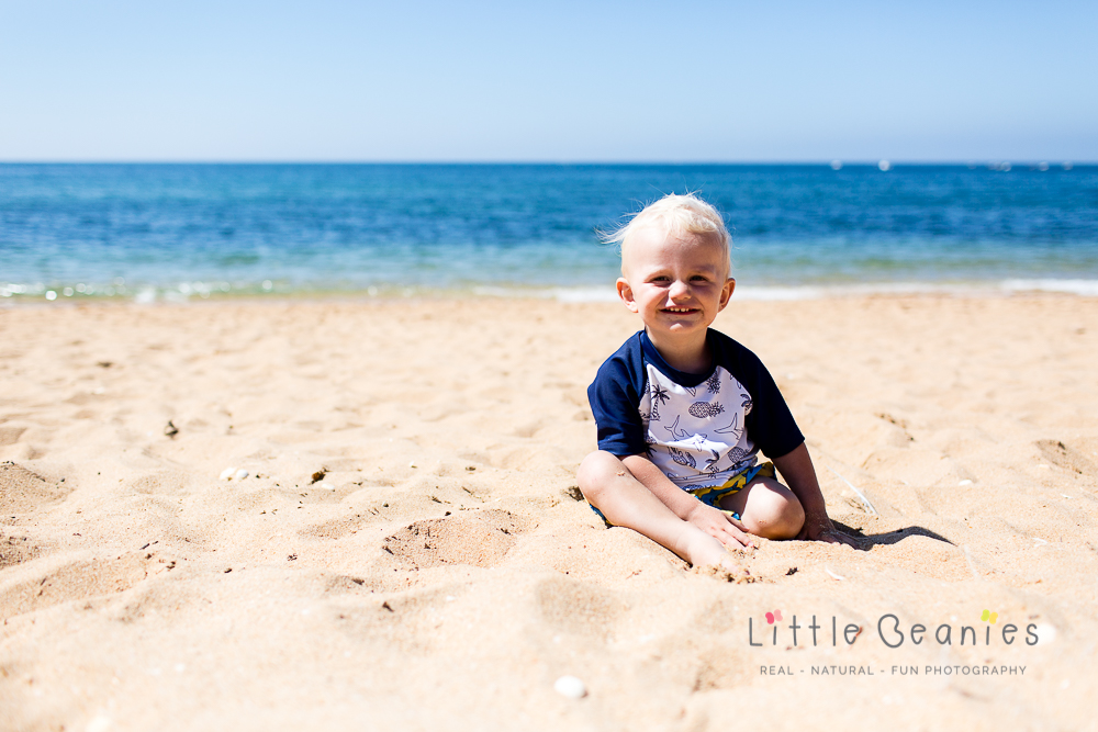 gorgeous boy on beach looking into see on a family photo shoot