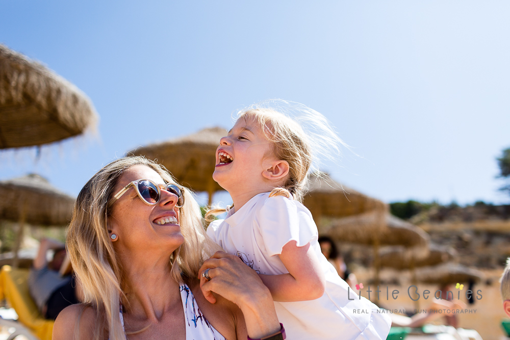 little girl laughing with mummy having photographs taken on beach