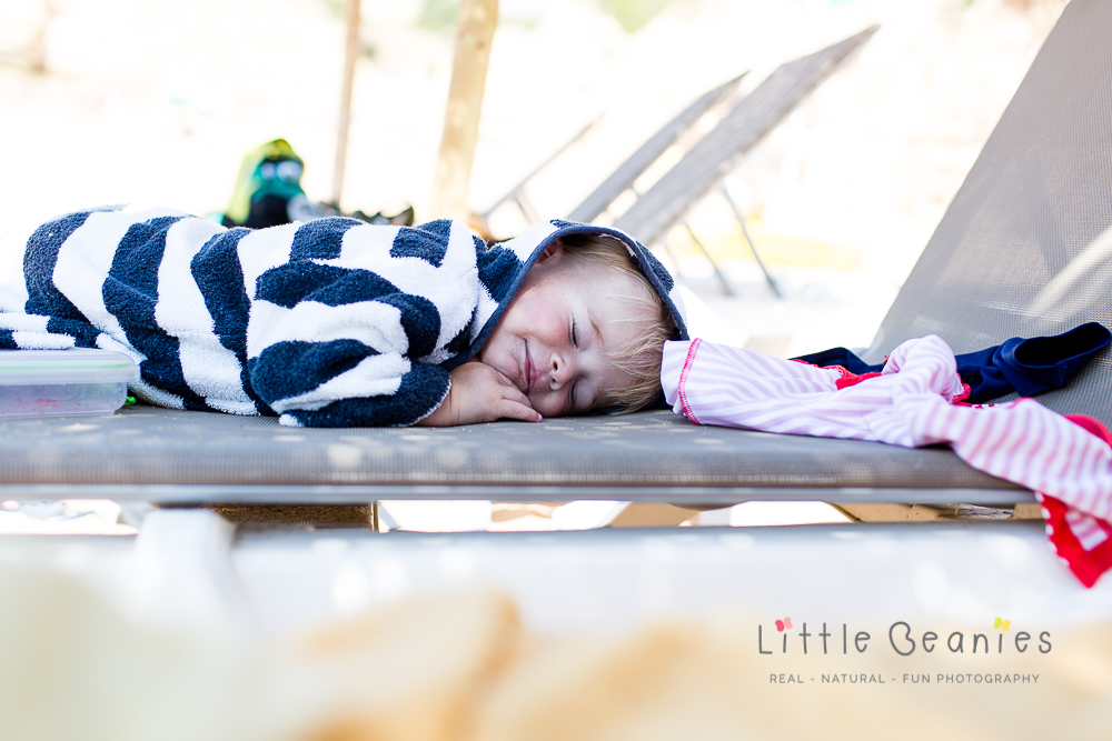 boy fast asleep on beach bed whilst having family photos captured