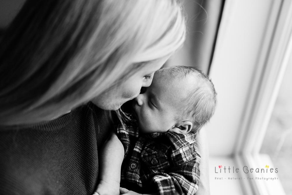 coventry newborn photographer taking photograph of mum and newborn baby by window
