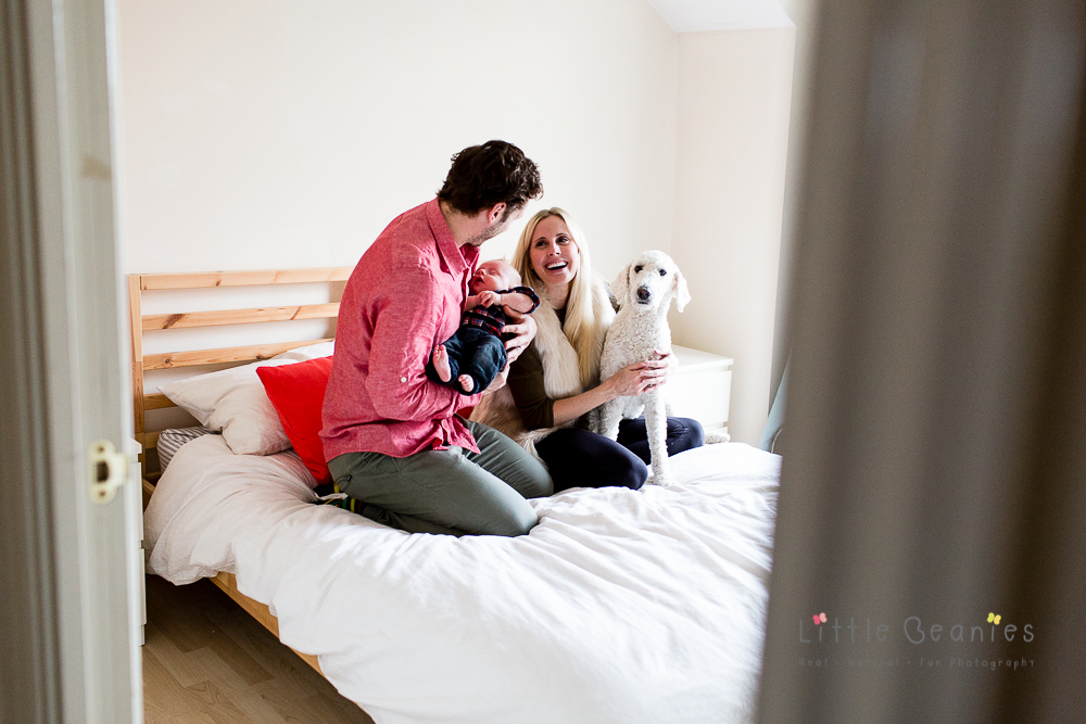 mum and dad with bay and dog on bed having photoshoot in coventry