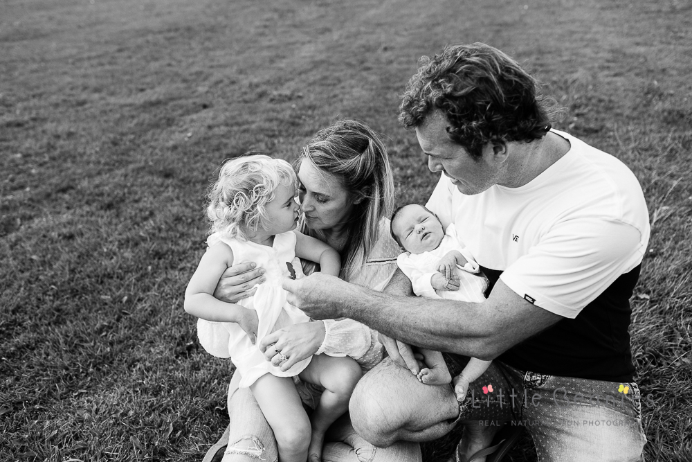 black and white photoshoot of family outside with newborn baby at home in Kenilworth